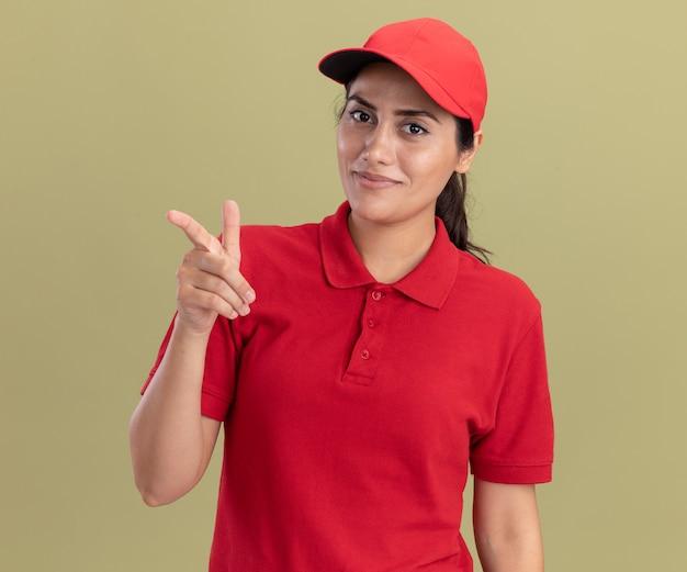 Улыбающаяся молодая доставщица в униформе с кепками перед камерой, изолированной на оливково-зеленой стене