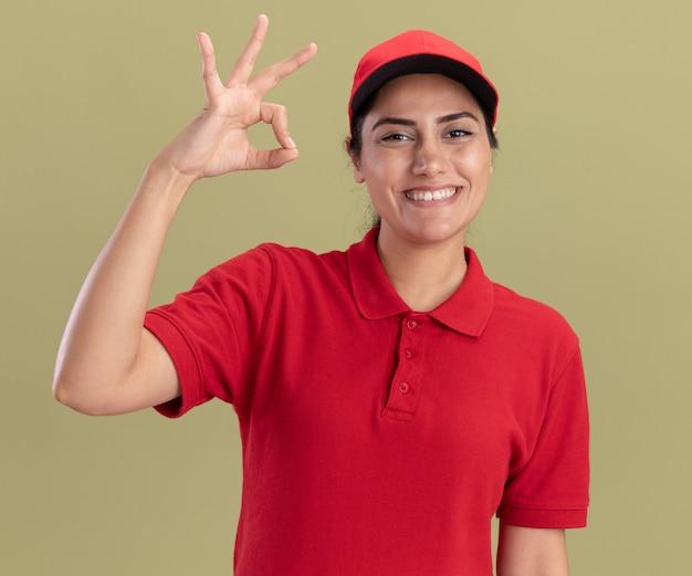 Улыбающаяся молодая доставщица в униформе с кепкой, показывающая нормальный жест, изолирована на оливково-зеленой стене