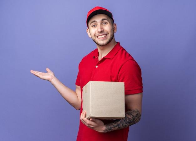 옆에 손으로 상자 포인트를 들고 모자와 유니폼을 입고 웃는 젊은 배달 남자 프리미엄 사진