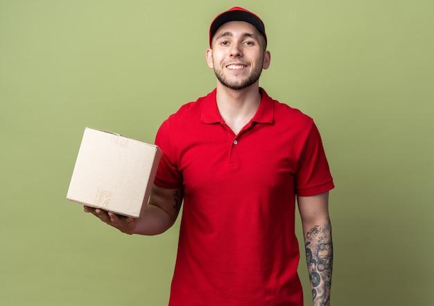 모자를 들고 상자를 들고 유니폼을 입고 웃는 젊은 배달 남자