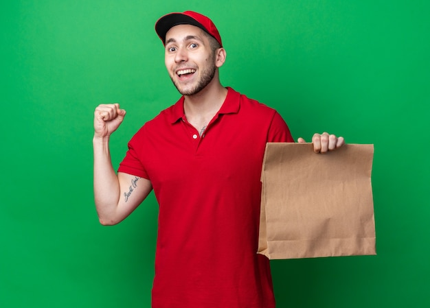 はいジェスチャーを示す紙のフードバッグを保持しているキャップと制服を着て笑顔の若い配達人