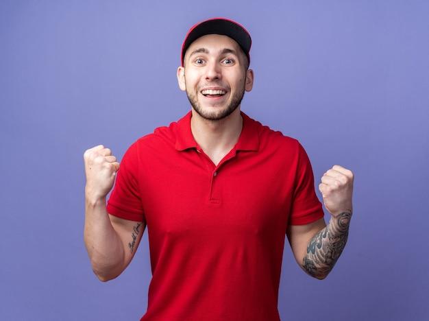 예 제스처를 보여주는 모자와 유니폼을 입고 웃는 젊은 배달 남자
