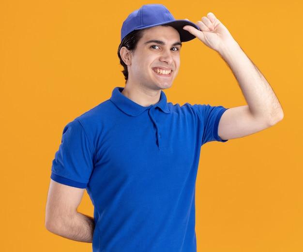 Sorridente giovane fattorino in uniforme blu e berretto che guarda davanti tenendo la mano dietro la schiena che afferra il berretto isolato sul muro arancione