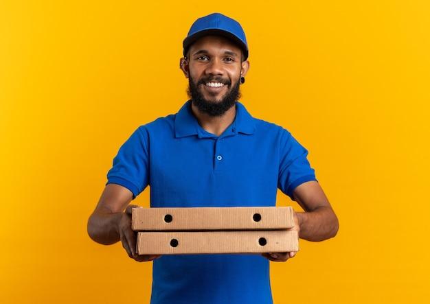 コピースペースとオレンジ色の壁に分離されたピザボックスを保持している若い配達人の笑顔