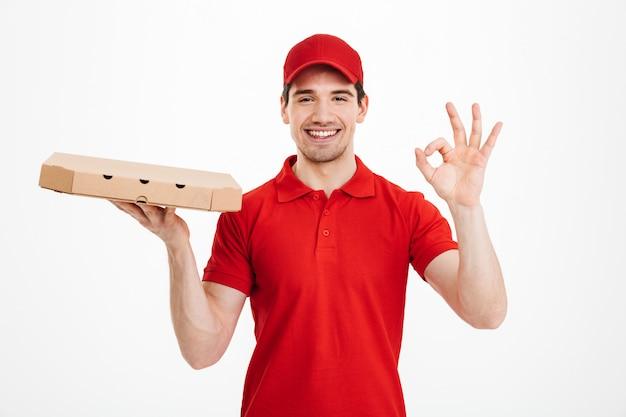 Улыбающийся молодой доставщик держит пиццу.