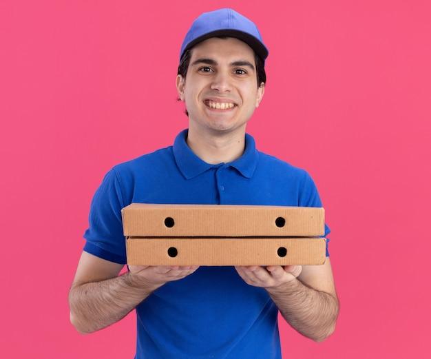 Улыбающийся молодой курьер в синей форме и кепке, держащий пакеты с пиццей, смотрящий вперед, изолированный на розовой стене
