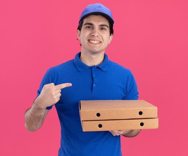 Улыбающийся молодой доставщик в синей форме и кепке держит упаковки с пиццей, глядя вперед, указывая на сторону, изолированную на розовой стене