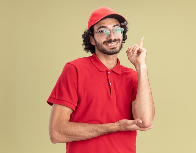 빨간 유니폼을 입은 웃고 있는 젊은 배달원과 올리브 녹색 벽에 고립된 앞을 가리키는 안경을 쓴 모자