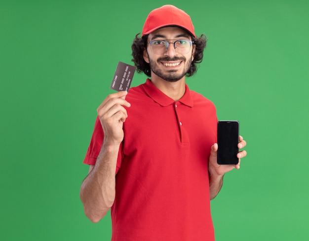 Улыбающийся молодой курьер в красной форме и кепке в очках показывает мобильный телефон и кредитную карту спереди, глядя вперед, изолированный на зеленой стене с копией пространства