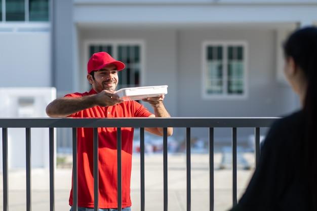 Улыбающийся молодой курьер в красной форме, держащий коробку, передает костюмер красивой женщины перед домом.