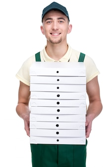 Smiling young delivery man is holding a pizza.