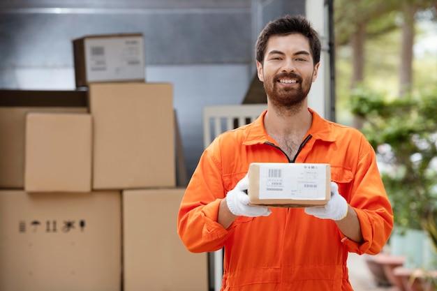 Sorridente giovane uomo di consegna che prepara i pacchi per la consegna