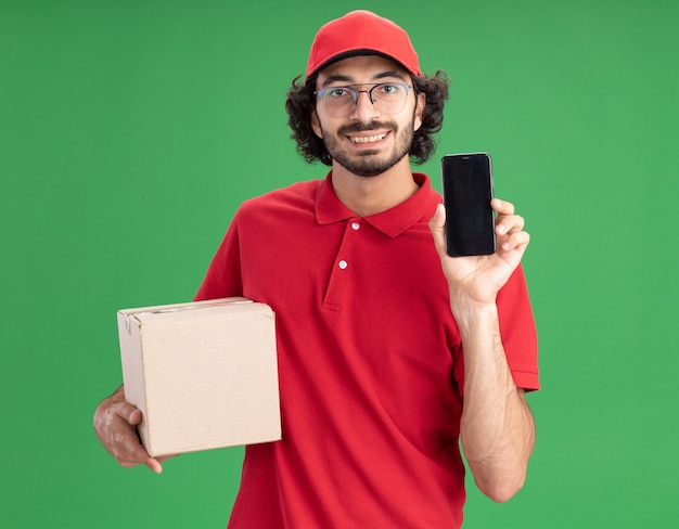 Smiling young delivery man in red uniform and cap wearing glasses holding cardbox showing mobile phone to front looking at front isolated on green wall