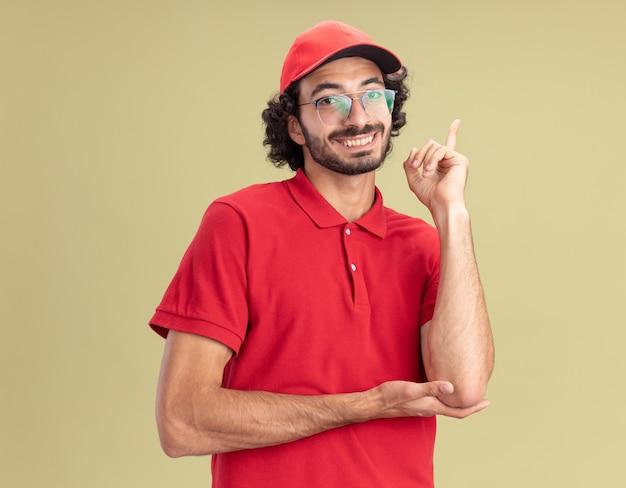 Sorridente giovane fattorino in uniforme rossa e berretto con gli occhiali guardando la parte anteriore rivolta verso l'alto isolata sulla parete verde oliva