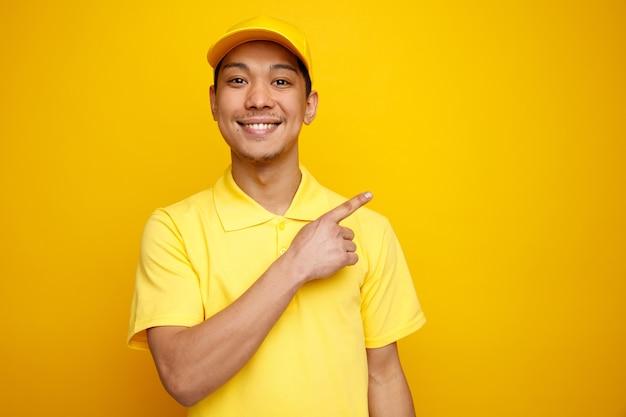 Улыбающийся молодой курьер в кепке и униформе, указывая вверх на угол