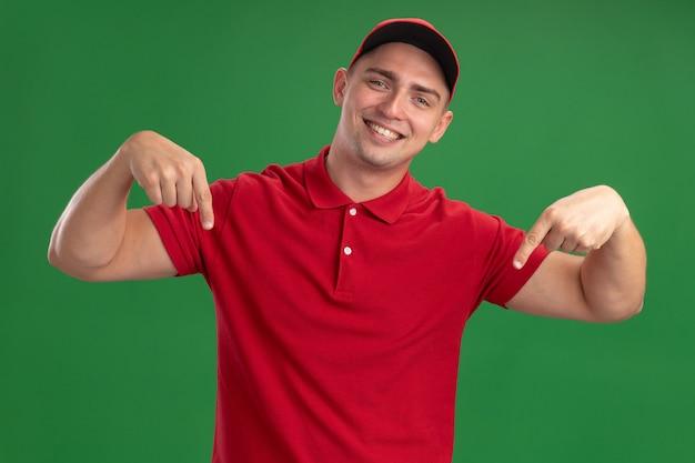 녹색 벽에 고립 다운에서 유니폼과 모자 포인트를 입고 웃는 젊은 배달 남자