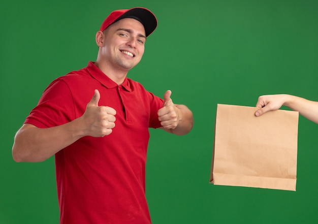 Smiling young delivery man wearing uniform and cap giving paper food package to client showing thumbs up isolated on green wall