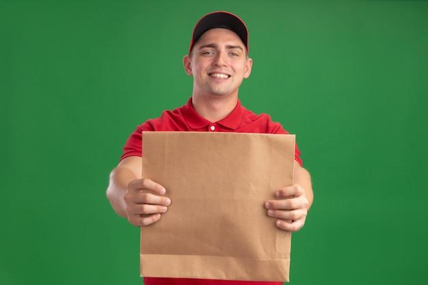 Sorridente giovane fattorino che indossa l'uniforme e cappuccio che tiene fuori il pacchetto di cibo di carta nella parte anteriore isolata sulla parete verde