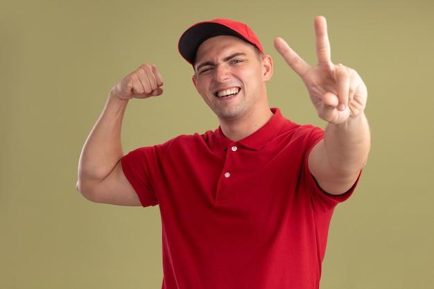 Sorridente giovane fattorino che indossa l'uniforme e cappuccio che mostra gesto di pace facendo un gesto forte isolato sulla parete verde oliva