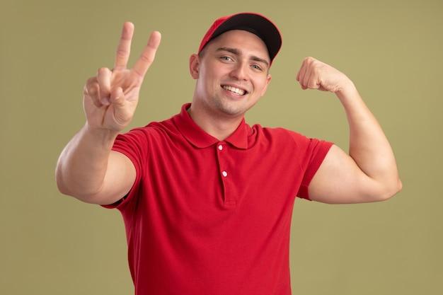 Sorridente giovane fattorino indossando l'uniforme e berretto che mostra il gesto di pace con un forte gesto isolato sulla parete verde oliva