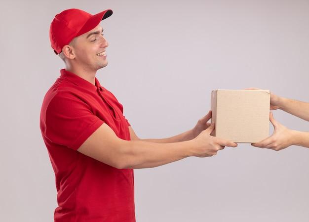 白い壁に隔離されたクライアントに箱を与えるキャップ付きの制服を着た笑顔の若い配達人