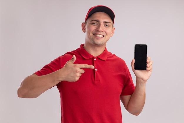 흰 벽에 고립 된 전화에서 모자 보유와 포인트와 유니폼을 입고 웃는 젊은 배달 남자