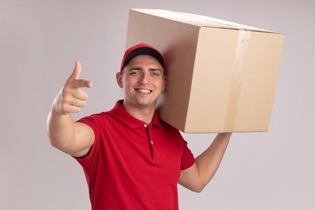 Sorridente giovane fattorino che indossa l'uniforme con cappuccio che tiene grande scatola sulla spalla e punti alla macchina fotografica isolata sulla parete bianca