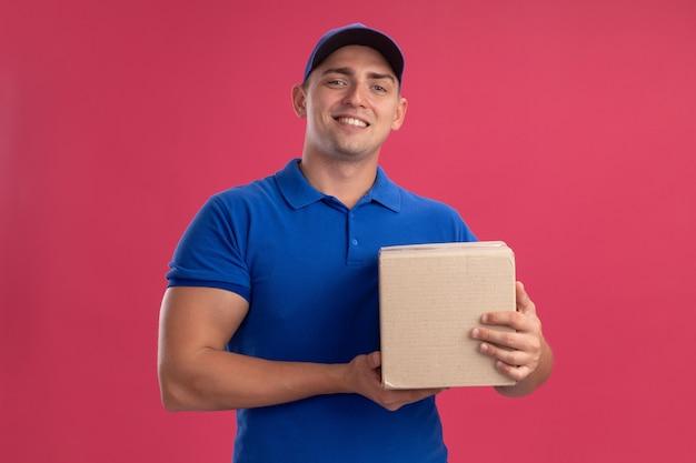 Улыбающийся молодой курьер в униформе с кепкой, держащей коробку, изолированную на розовой стене