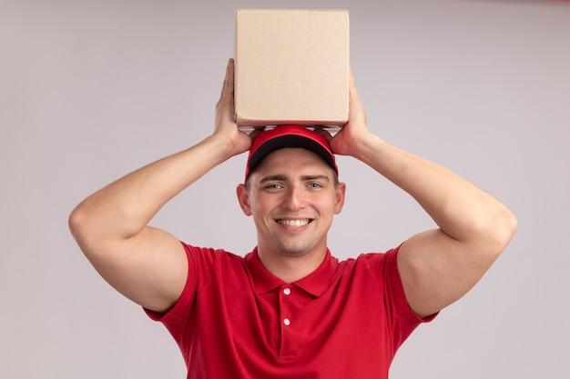 Улыбающийся молодой доставщик в униформе с кепкой, держащей коробку на голове, изолированную на белой стене