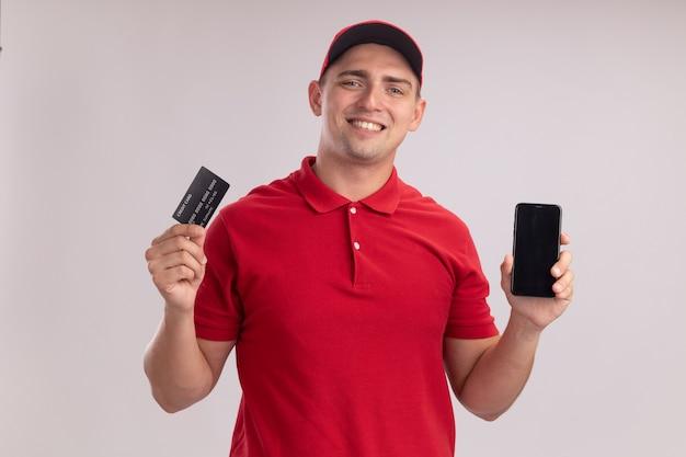 흰 벽에 고립 된 전화로 신용 카드를 들고 모자와 유니폼을 입고 웃는 젊은 배달 남자