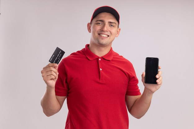 Smiling young delivery man wearing uniform with cap holding credit card with phone isolated on white wall
