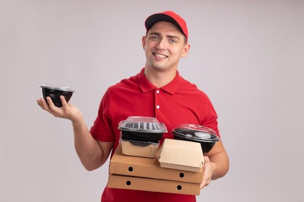 흰 벽에 고립 된 피자 상자에 음식 용기를 들고 모자와 유니폼을 입고 웃는 젊은 배달 남자