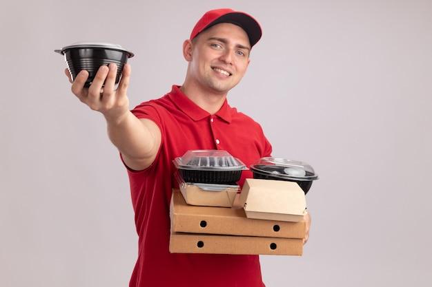 Sorridente giovane fattorino che indossa l'uniforme con cappuccio che tiene i contenitori per alimenti sulle scatole per pizza tenendo fuori il contenitore per alimenti isolato sul muro bianco