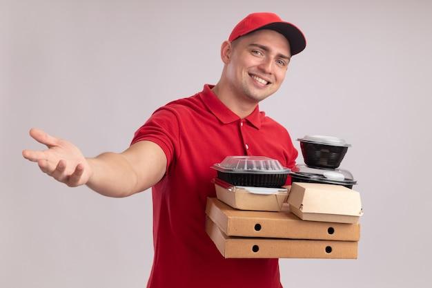 Sorridente giovane fattorino che indossa l'uniforme con cappuccio che tiene contenitori di cibo sulle scatole per pizza tendendo la mano alla macchina fotografica isolata sul muro bianco