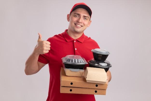Sorridente giovane fattorino che indossa l'uniforme con cappuccio che tiene i contenitori per alimenti sulle scatole per pizza che mostra pollice in alto isolato sul muro bianco