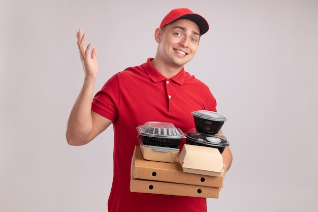 Smiling young delivery man wearing uniform with cap holding food containers on pizza boxes spreading hand isolated on white wall