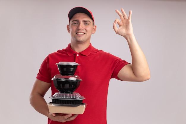 Sorridente giovane fattorino indossando l'uniforme con cappuccio che tiene i contenitori di cibo che mostra il gesto giusto isolato sulla parete bianca