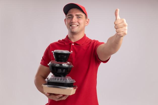 白い壁に分離された親指を示す食品容器を保持しているキャップと制服を着て笑顔の若い配達人