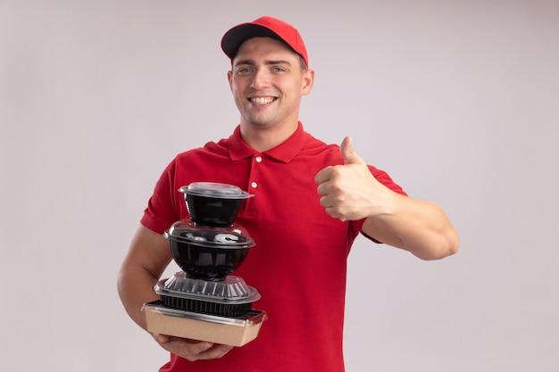 Sorridente giovane fattorino indossando l'uniforme con cappuccio che tiene i contenitori per alimenti che mostra il pollice in su isolato sulla parete bianca