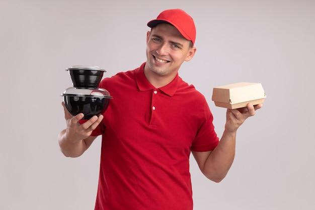 Sorridente giovane fattorino che indossa l'uniforme con cappuccio che tiene contenitori per alimenti con pacchetto di carta alimentare isolato sulla parete bianca