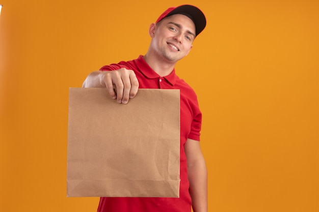 Smiling young delivery man wearing uniform with cap holding out paper food package at front isolated on orange wall