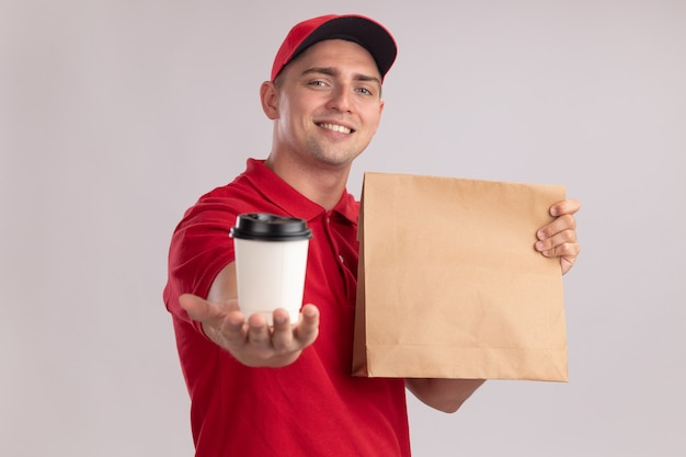 Smiling young delivery man wearing uniform with cap holding paper food package and holding out cup of coffee at front isolated on white wall