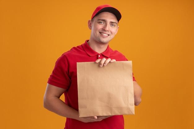 Sorridente giovane fattorino indossando l'uniforme con cappuccio che tiene il pacchetto di cibo di carta isolato sulla parete arancione