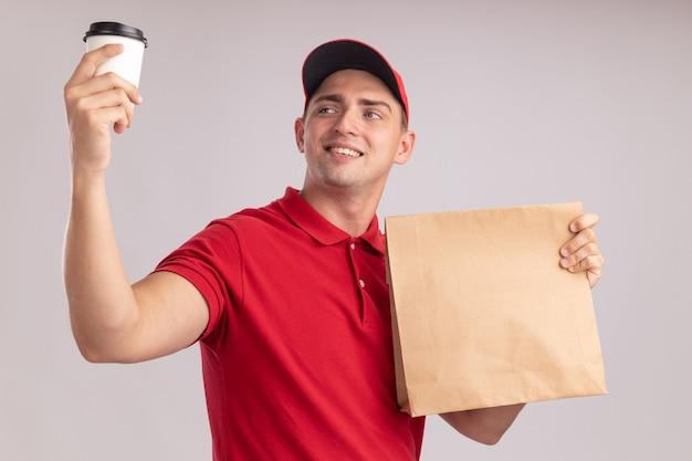 Sorridente giovane fattorino indossando l'uniforme con cappuccio che tiene il pacchetto di cibo di carta alzando e guardando la tazza di caffè isolata sulla parete bianca