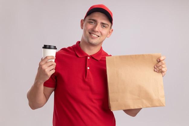 Sorridente giovane fattorino che indossa l'uniforme con cappuccio che tiene il pacchetto di cibo di carta con una tazza di caffè isolato sulla parete bianca