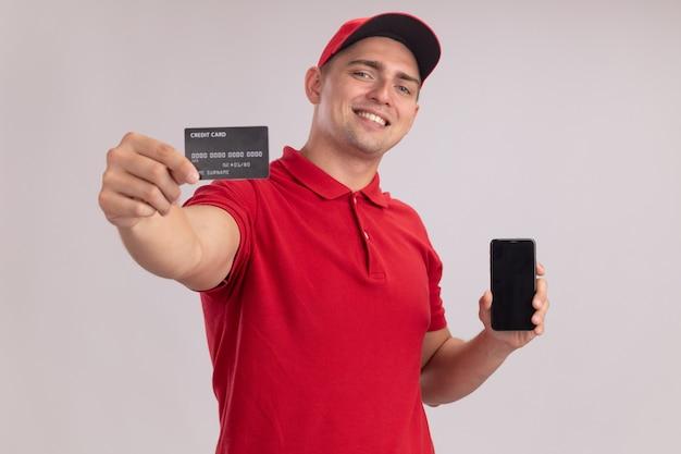 Sorridente giovane fattorino indossando l'uniforme con tappo tenendo il telefono e porgendo la carta di credito nella parte anteriore isolata sul muro bianco