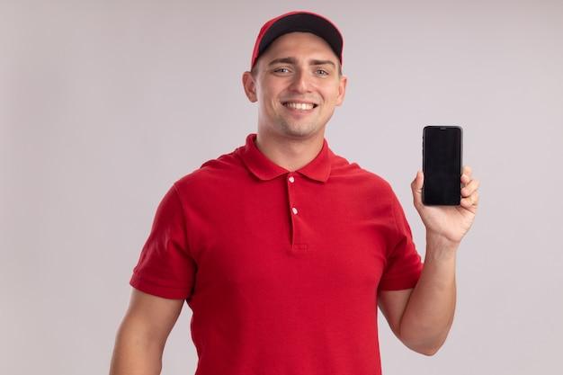 흰 벽에 고립 된 전화를 들고 모자와 유니폼을 입고 웃는 젊은 배달 남자