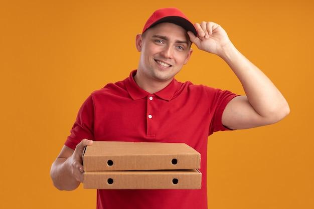 오렌지 벽에 고립 된 피자 상자를 들고 모자와 유니폼을 입고 웃는 젊은 배달 남자