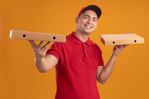 Улыбающийся молодой доставщик в униформе с кепкой держит коробки для пиццы, изолированные на оранжевой стене