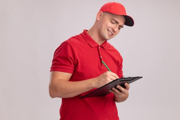 흰 벽에 고립 된 클립 보드에 뭔가 쓰는 모자와 유니폼을 입고 웃는 젊은 배달 남자